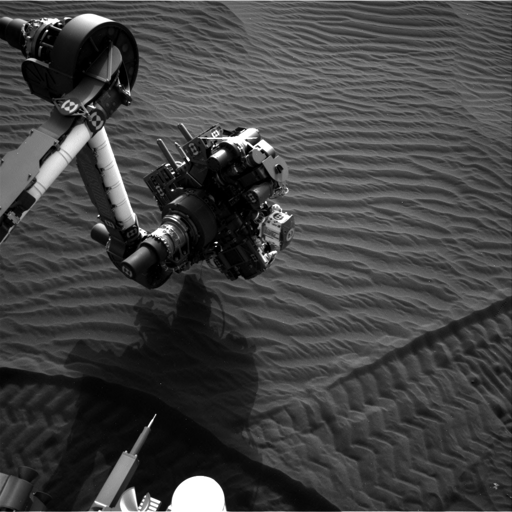Navcam view showing the rover arm analyzing dark sand dunes