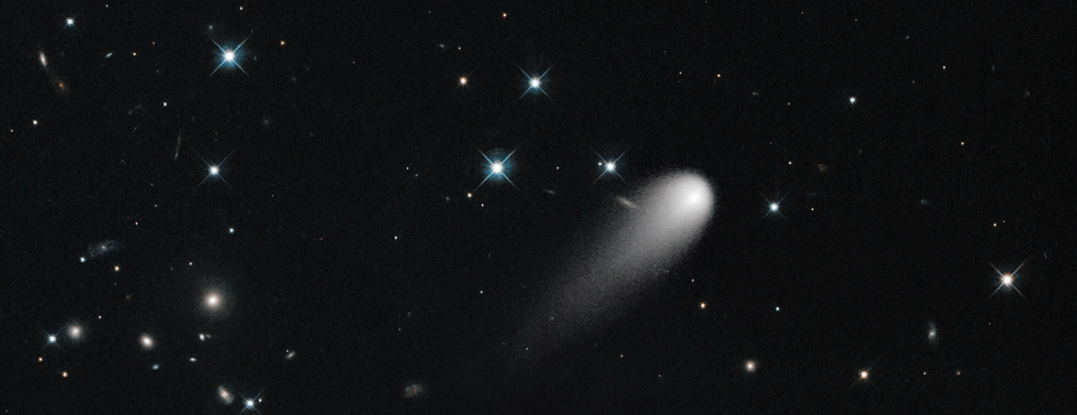 Comet ISON (C/2012 S1) streaks across the darkness of space, with shining stars and distant galaxies in the background