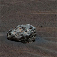 On a surface of small-grained martian 'soil' rests a mis-shapen oblong rock, now identified as an iron meteorite.  Its surface is smooth and dark, with many irregular pits gouging the surface.  The large pits are also smooth, and are relics of dramatic erosion that occurred during the meteorite's atmospheric entry.  Some of the pits are now filled with reddish dust.