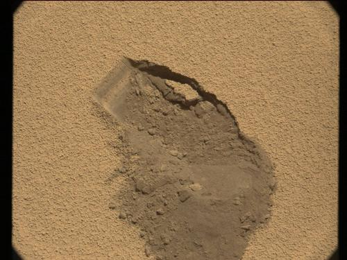 A Sol 61 raw image from the right Mast Camera, shows the location from which Curiosity's first scoop of soil was collected.
