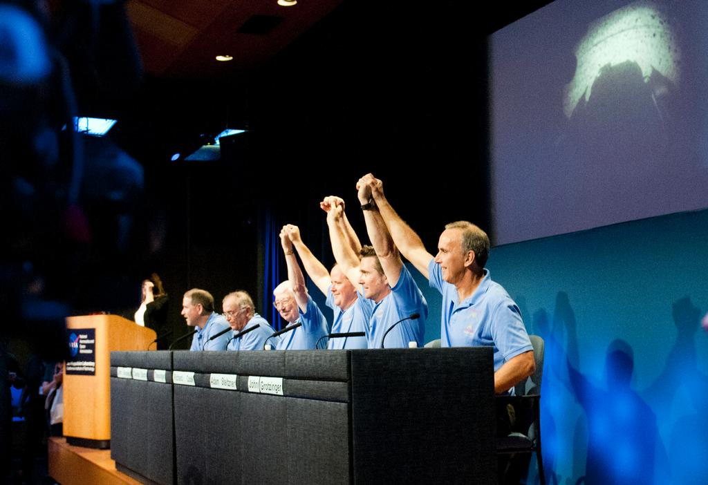 Mars Science Laboratory mission scientists, flight controllers, managers and administrators raise their hands to a cheering crowd at a news conference following the successful landing of NASA's Curiosity rover on Mars.