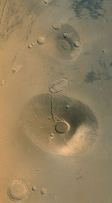 Taken in March 2002, this Surveyor image shows two inactive, ancient Mars volcanoes. The upper one is called Uranius Tholus, the lower one Ceraunius Tholus.