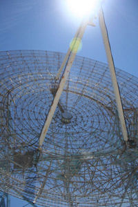 This picture shows a close-up view of an antenna that is a circular apparatus made out of intricate wiring that looks like a gigantic industrial fan. The camera angle is from the ground looking up, and the far right and far left curves of the antenna are not visible in the picture. Three 6-meter (20-foot) long, white metal beams jut off of the middle of the antenna in a tepee shape, pointing out and up to the sky. The triangular beams intersect at a point at the top center of the image right where the midday sun beams brightly in a white, glowing circle the size of a quarter. A clean, blue sky covers the background of the entire image and can be seen through the wire mesh antenna.