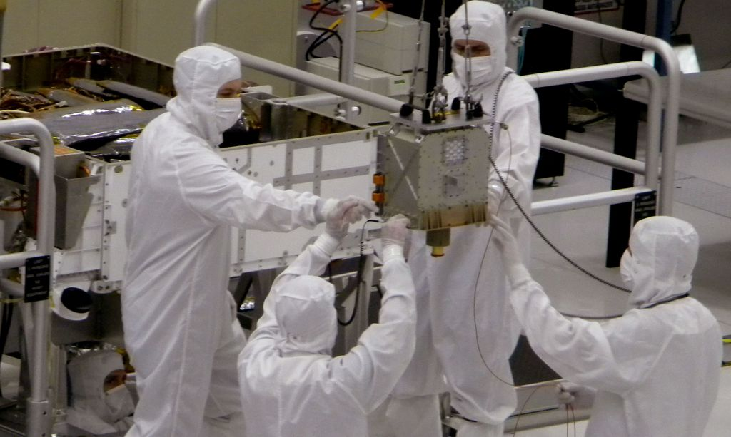 Members of NASA's Mars Science Laboratory team carefully steer the hoisted Chemistry and Mineralogy (CheMin) instrument during its installation into the Mars rover, Curiosity.