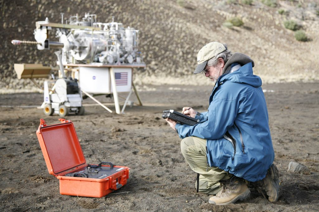 This image shows a miniaturized laboratory, in an orange case, in use during an expedition to the Mauna Kea volcano in Hawaii.