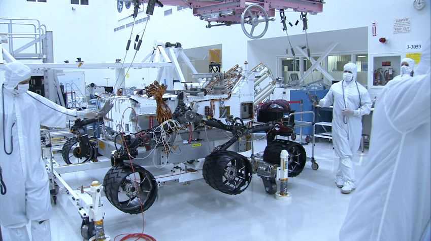 "In this picture, the Curiosity rover is sitting on top of six shiny wheels. The picture was taken from the side of the rover and only four wheels are visible. The wheels have a black coating which makes them slip resistant. On the right of the rover is an engineer who is wearing a white ""bunny suit"" to prevent him from getting any unwanted Earth microbes onto the rover. The engineer is holding one of the lift cables used to put the rover onto the wheels. A pink heavy-lift crane is visible over the rover. The crane is used to lift the rover body within the room. Behind the rover, lots of lab equipment and other parts are scattered around the clean room."