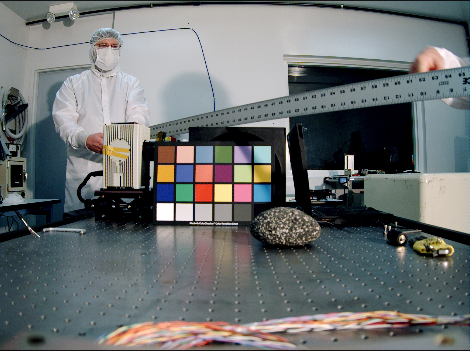 The Mars Descent Imager for NASA's Mars Science Laboratory took this image inside the Malin Space Science Systems clean room in San Diego, Calif., during calibration testing of the camera in June 2008. It shows the instrument's deputy principal investigator, Ken Edgett, holding a six-foot metal ruler that was used as a depth-of-field test target.