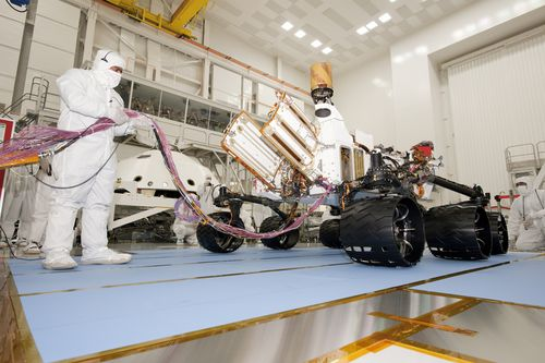 A test operator in clean-room garb holds umbilical cables for NASA's Mars rover Curiosity during the rover's first drive test, on July 23, 2010.