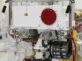 This image shows a close-up of the rover's 'head.' At the top is a white box structure with a large red circle (the rover's laser called ChemCam) to the right. Beneath the box are two cameras, which will provide views of the Martian surface. They are covered with protective silvery material.