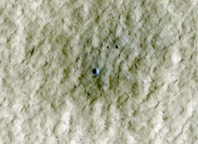 At the center of this view of an area of mid-latitude northern Mars, a fresh crater about 6 meters (20 feet) in diameter holds an exposure of bright material, blue in this false-color image.