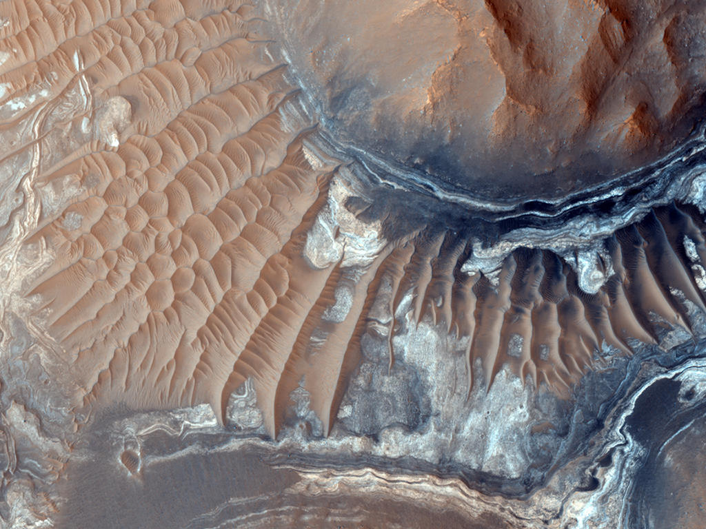 This image reveals exposed layers in Noctis Labyrinthus which may contain signatures of iron bearing sulfates and phyllosilcate (clay) minerals.