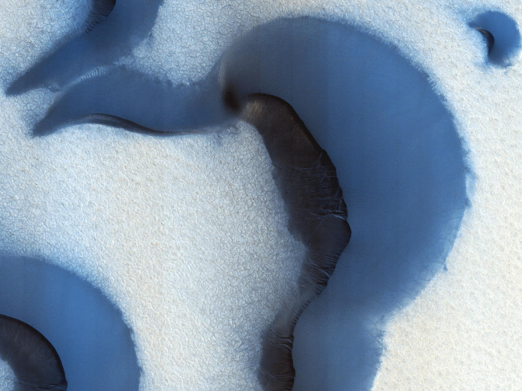 This picture was taken during the Martian summer with only small patches of ice remaining at the surface; they show up as bright, somewhat blue, spots on slopes that provide some shading from the Sun.