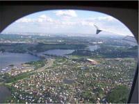 This picture was taken from inside an airplane as it was flying over Moscow at about 4,000 feet with a few clouds in the sky. The left wing juts into view and the flaps are down. The sun is shining on the community, which is speckled with hundreds of little farm-style houses, with lush green grass and trees surrounding all the buildings in the foreground. In the distance, a wide, dark blue river snakes across the ground, with a large bridge crossing over the center of the river. A few boats are docked near a road. In the far distance, thousands of buildings seemingly go on forever.