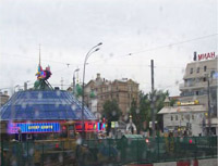 This image is a snapshot of Moscow from a bus on a rainy day. A large, dome-like structure with blue, red, and pink neon signs houses a casino to the left in the picture; a fast-food restaurant sign blazes through the raindrops to the right; an old green and gold church peeks through the background; and a road construction zone complete with big, yellow Earth-mover trucks sits in the foreground.