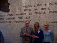 This picture is of Igor Mitrofanov, Nora Kelly and Cindy Schulz standing in front of a quote in Russian by Tsiolokovsky, who was a pioneer of rocketry in Russia. Igor is a tall man with gray hair and glasses, wearing a grey blazer and red tie. Nora is about 5'9, has long blond hair and is wearing glasses and a royal blue sweater. Cindy is about 5'7 and wears a light blue sweater set.