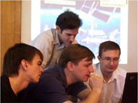This image is of four young Russian engineers (each between 20 -25 years old) huddling together, intently looking at a laptop screen, discussing their next space mission. Projected on a large screen behind the team is a picture of the space shuttle docked with the International Space Station orbiting the blue skies and oceans of Earth.