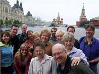 This picture is of fourteen adults smiling and huddling together in front of buildings in Red Square in Moscow. The sky is grey and most people wear jackets. In the background is a colorful church with eight onion-shaped domes called St. Basil's. A large red brick building with a black and gold clock is to the right with a tall tower and a star on top. To the left is an enormous white building that spans the width of the town square (about 200 feet) with scaffolding in front.