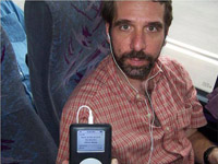 This picture of Jeff Plaut was taken inside a bus. Jeff is in his late-thirties, has brown hair and a beard, and wears a red, short-sleeved, button-up shirt. He's looking directly into the camera, slightly smiling, and holding up a portable music player to show the digital display, which says, 'Back in the U.S.S.R. The Beatles. White Album.' Small white headphones are in Jeff's ears and attach by a chord to the music player.