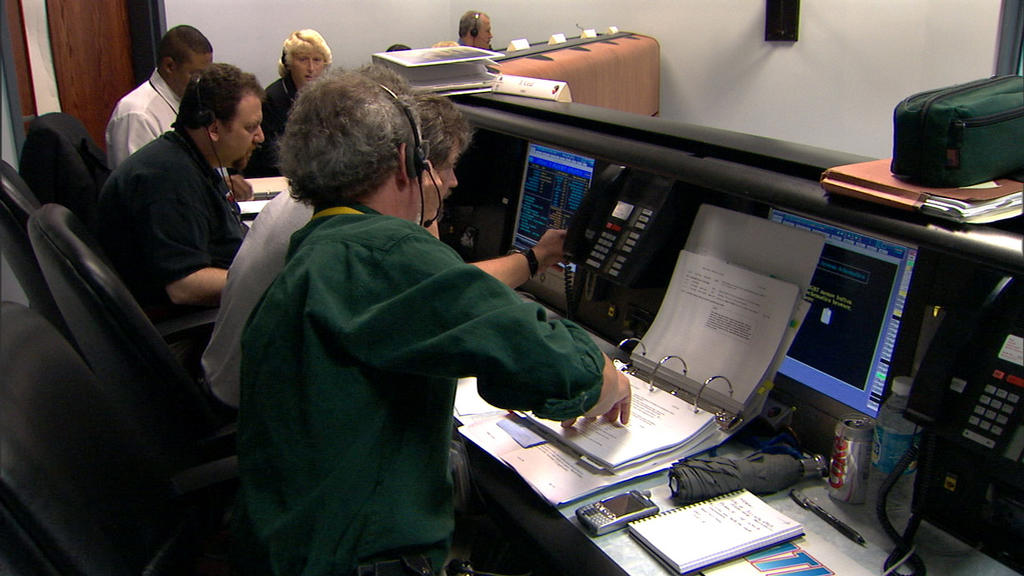 In this image, six individuals sit at consoles in front of computers during a launch rehearsal for the Mars Reconnaissance Orbiter mission. Launch vehicle manager Arden Acord (a gray-haired, Caucasian middle-aged man with a goatee) points to data on project manager Jim Graf's computer. Graf is a brown-haired Caucasian man in his fifties. Flight system manager Howard Eisen sits to Graf's left. He is a Caucasian man with brown hair and a goatee. Next to Eisen are two Lockheed Martin employees, one of whom is Tammy Harrington, the mission integration manager. She is a blond woman in her forties.