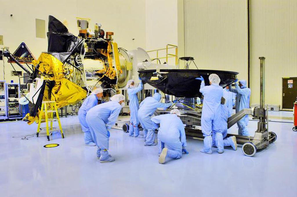 Technicians and engineers dressed from head to toe in blue coveralls (called 'bunny suits') prepare the Mars Reconnaissance Orbiter's large, black high-gain antenna (that resembles a satellite dish) to be mated with the body of the spacecraft. The bus of the spacecraft with nearly all of its instruments in place, sits just to the left of the people pictured. Parts of the orbiter are covered in gold, shiny thermal blanketing. Facing directly upward is the spacecraft's huge Hi-RISE camera covered in black protective blanketing.