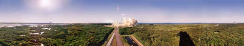 In this panoramic view, the launch of an Atlas V rocket is seen from a distance, down a road that leads to the launch pad at launch complex 41 at Cape Canaveral Air Station, Florida. In the middle of the image, the rocket appears as a small, thin line ascending into the sky. Billowy smoke surrounds the launch pad and the green of the marshy land around the complex is brilliant. The sun is shining brightly in the left corner of the image and the blue water of the Atlantic Ocean is visible just behind the launch complex.