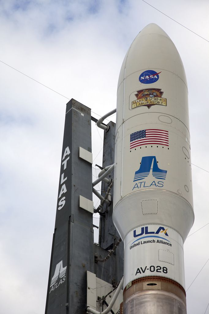 The NASA and Mars Science Laboratory (MSL) logos appear above the American flag and Atlas logo on the payload fairing atop the 197-foot-tall United Launch Alliance Atlas V rocket.