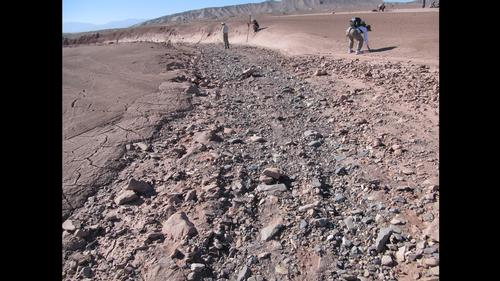 This image shows a dry streambed on an alluvial fan in the Atacama Desert, Chile, revealing the typical patchy, heterogeneous mixture of grain sizes deposited together.
