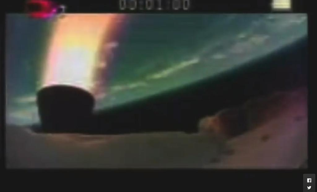 The picture show the LDSD test vehicle and an engine burn in orange/red, with Earth as a blue-green orb in the background.