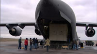 In this image, more than a dozen people stand, in winter coats, behind a huge, gray military C-17 cargo plane. From this vantage point, the plane resembles a huge shark with its mouth wide open. Inside the 'mouth' is one of the large boxes that contain the Mars Reconnaissance Orbiter. The wings of the plane jut out from both sides. The sky is cloud-covered.
