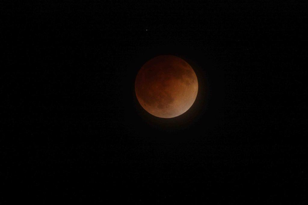 This is an image of the moon during the total lunar eclipse on April 15, 2014. In this image, the moon appears bright orange and is centered on a black sky. Mars is seen a tiny white-red dot on the upper left-hand side of the moon.