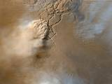 This image shows a turbulent mass of thick, roiling, red Martian dust rising from a network of canyons and flowing diagonally toward the lower left corner of the frame. Above the storm front, wispy, white clouds of water ice trail off toward the left, toward the bottom of the frame, toward the top of the frame, and toward the upper right corner of the frame.