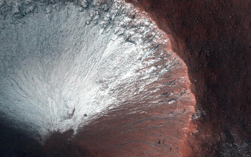 This image shows frost on a crater slope. The white frost covers nearly the top side of the crater, while the bottom part appears reddish in color.