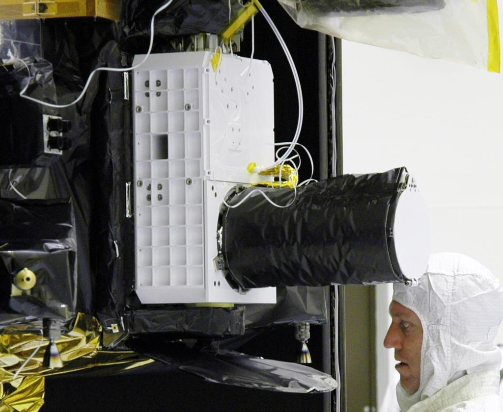 With the Compact Reconnaissance Imaging Spectrometer for Mars (CRISM) instrument just above his head, a technician at NASA's Kennedy Space Center works on the Mars Reconnaissance Orbiter spacecraft in July 2005.