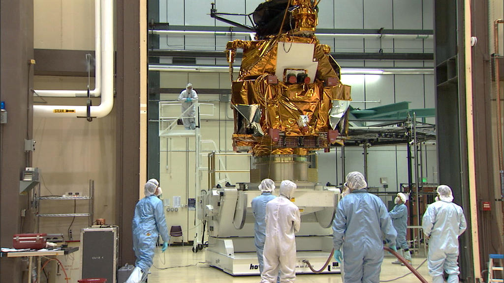 A group of eight engineers and technicians dressed in white and blue cleanroom coveralls and bonnets (called 'bunny suits') stand and watch as the large, boxy bus of the Mars Reconnaissance Orbiter is lifted by a large, white mechanism. The bus is covered in protective, gold thermal blanketing.