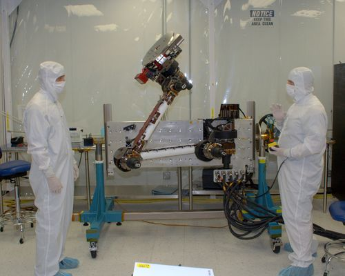 In this photo, two engineers from NASA Jet Propulsion Laboratory and Alliance Spacesystems are standing in a white room on either side of the Mars Science Laboratory rover's robotic arm. They are dressed in white 'bunny suits,' and are covered from head to toe wearing white face masks to protect the equipment. The arm is bent at the 'elbow' and raised high in the air about two feet higher than the engineer on the left. The engineer on the right holds a control box that maneuvers the arm for testing.
