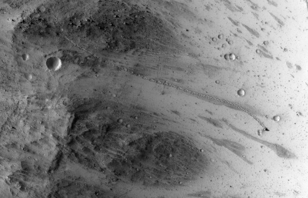 A path resembling a dotted line from the upper left to middle right of this image is the track left by an irregularly shaped, oblong boulder as it tumbled down a slope on Mars before coming to rest in an upright attitude at the downhill end of the track.