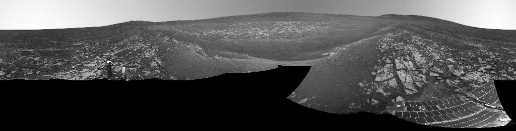 A black and white panoramic image showing layers of rocks on the right and left side of the image. The rover's antenna is visible on the bottom-right and the solar panels can be seen on the bottom right.