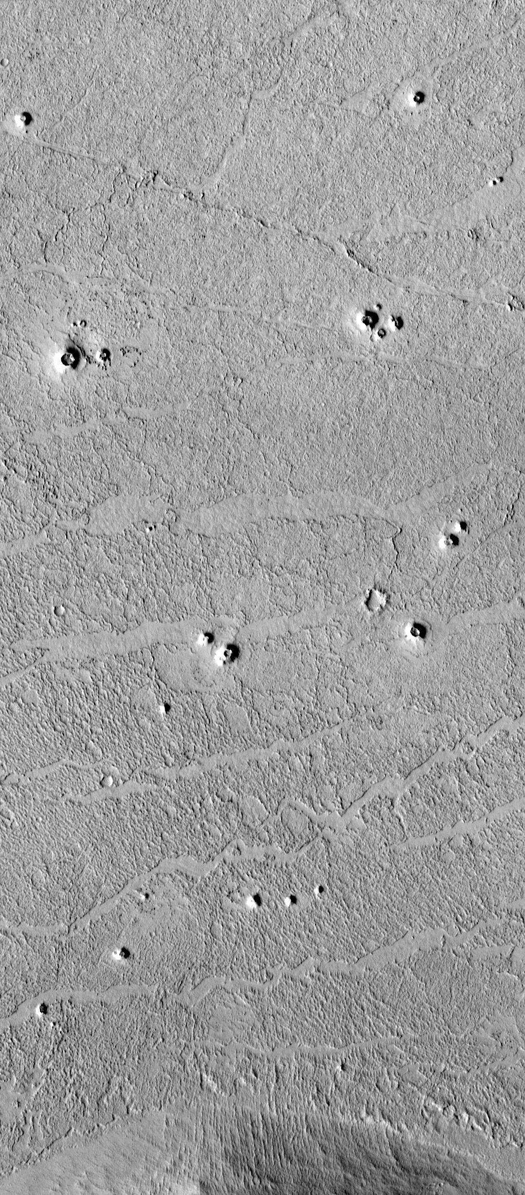 "High-resolution images from the Mars Global Surveyor (MGS) Mars Orbiter Camera (MOC) have revealed small cone-shaped structures on lava flows in southern Elysium Planitia, Marte Valles, and northwestern Amazonis Planitia in the northern hemisphere of the red planet. The most likely interpretation of these cones is that they may be volcanic features known as ""pseudo craters"" or ""rootless cones."" They share several key characteristics with pseudo craters on Earth: they are distributed in small clusters independent of structural patterns, are superimposed on fresh lava flows, and they do not appear to have erupted lavas themselves"