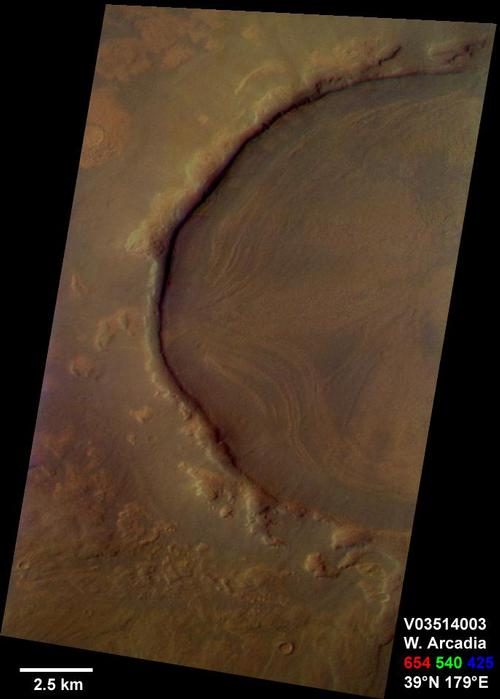 This is a Mars Odyssey visible color image of an unnamed crater in western Arcadia Planitia (near 39 degrees N, 179 degrees E). The crater shows a number of interesting internal and external features that suggest that it has undergone substantial modification since it formed. These features include concentric layers and radial streaks of brighter, redder materials inside the crater, and a heavily degraded rim and ejecta blanket. The patterns inside the crater suggest that material has flowed or slumped towards the center. Other craters with features like this have been seen at both northern and southern mid latitudes The distribution of these kinds of craters suggests the possible influence of surface or subsurface ice in the formation of these enigmatic features. The image was taken on September 29, 2002 during late northern spring. This is an approximate true color image, generated from a long strip of visible red (654 nm), green (540 nm), and blue (425 nm) filter images that were calibrated using a combination of pre-flight measurements and Hubble images of Mars. The colors appear perhaps a bit darker than one might expect; this is most likely because the images were acquired in late afternoon (roughly 4:40 p.m. local solar time) and the low Sun angle results in an overall darker surface.