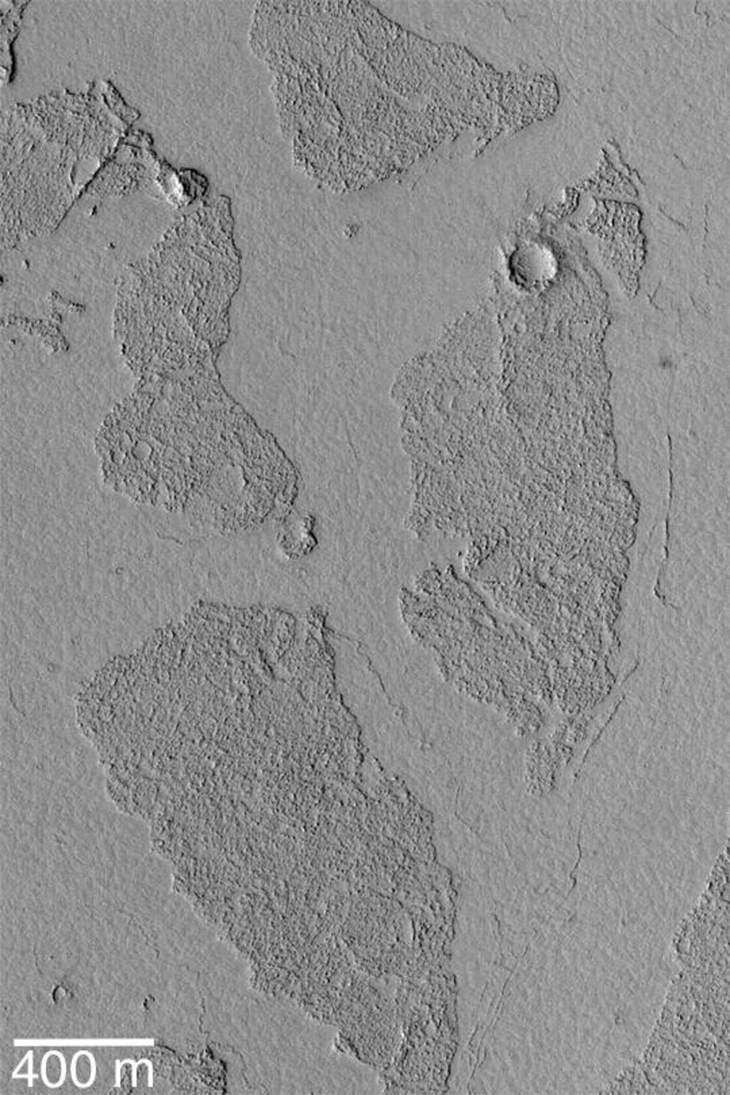 The Marte Vallis system, located east of Cerberus and west of Amazonis Planitia, is known for its array of broken, platy flow features. This Mars Global Surveyor (MGS) Mars Orbiter Camera (MOC) image shows a close-up view of some of these plates; they appear to be like puzzle pieces that have been broken apart and moved away from each other. The Mars science community has been discussing these features for the past several years--either the flows in Marte Vallis are lava flows, or mud flows. In either case, the material was very fluid and had a thin crust on its surface. As the material continued to flow through the valley system, the crust broke up into smaller plates that were then rafted some distance down the valley. This picture is located near 6.9°N, 182.8°W. It is illuminated by sunlight from the left.