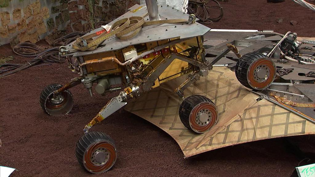 "This still image illustrates what the Mars Exploration Rover Spirit will look like as it rolls off the northeastern side of the lander on Mars. The image was taken from footage of rover testing at JPL's In-Situ Instruments Laboratory, or ""Testbed."""