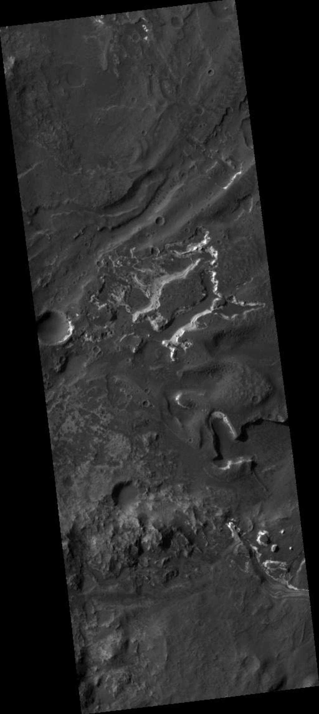 "This HiRISE image covers the southwest portion of the terraces and floor of Holden Crater situated in southwest Margaritifer Terra. The HiRISE sub-frame shows the most clearly-evident image of a megabreccia on Mars. Breccia is a rock typically consisting of rock fragments of various sizes and shapes that have been broken, tumbled and cemented together in sudden geologic event (e.g., a landslide, a flashflood or even an impact-cratering event). If it were not for the dark sandy dunes dispersed through out the sub-image, this image could easily fool an expert into thinking that this image is actually a photograph of a hand sample of an impact breccia. The prefix ""mega"" implies that the breccia in the sub-image consists of clasts, or rock fragments, that are typically larger than a large house or a building. The rectangular megaclast near the center of the image is a colossal 50 x 25 meters (~150 X 75 feet). As mentioned in the transition image caption for Holden crater (TRA_000861_1530), the crater likely experienced extensive modification by running water, which is supported by observations of drainage and deposition into the crater from a large channel (Uzboi Valles) breaching Holden's southwest rim. While it is possible that the megabreccia formed from a catastrophic release of water into the crater, a more likely possibility is that it formed from the impact that created the approx. 150 km-in-diameter Holden crater. Popigai Crater, a terrestrial crater of half the size of Holden, possesses a similar occurrence of megabreccia with a similar range in megaclast size to the Holden crater example. An impact-generated megabreccia deposit, as observed in terrestrial craters, typically lies beneath the crater floor, so the exhumation of the megabreccia may be the result of down-cutting and erosion of water that once flowed through Uzboi Valles."