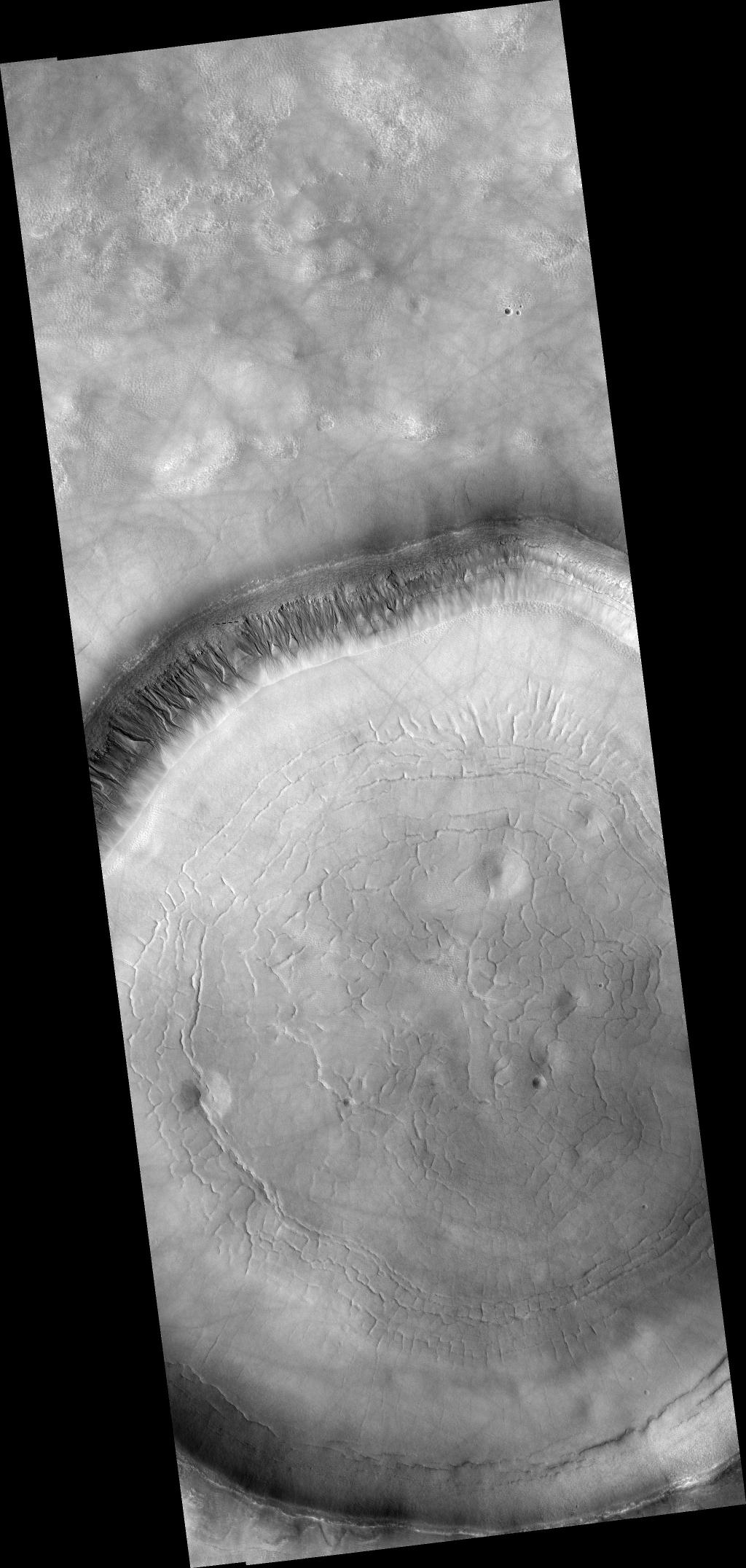 HiRISE image (PSP_001942_2310) shows a crater approximately 11 km (7 miles) in diameter, located in Acidalia Planitia, part of the Northern Plains. Several features in and around this crater are suggestive of fluids and ice at and near the surface. 