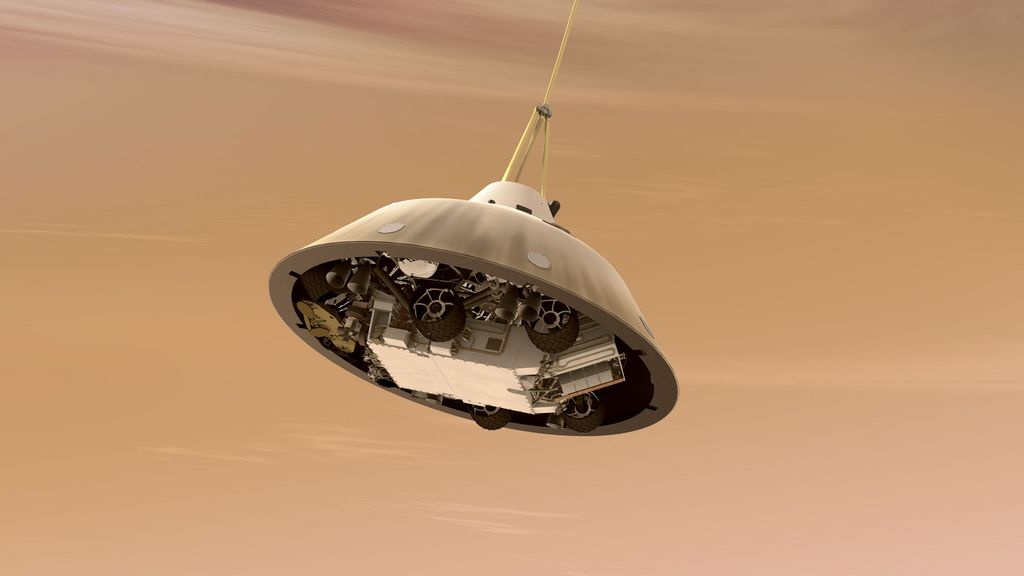 This is an artist's concept of NASA's Curiosity rover tucked inside the Mars Science Laboratory spacecraft's backshell while the spacecraft is descending on a parachute toward Mars.