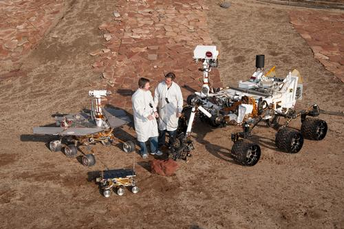 Two spacecraft engineers stand with a group of vehicles providing a comparison of three generations of Mars rovers developed at NASA's Jet Propulsion Laboratory, Pasadena, Calif. The setting is JPL's Mars Yard testing area.