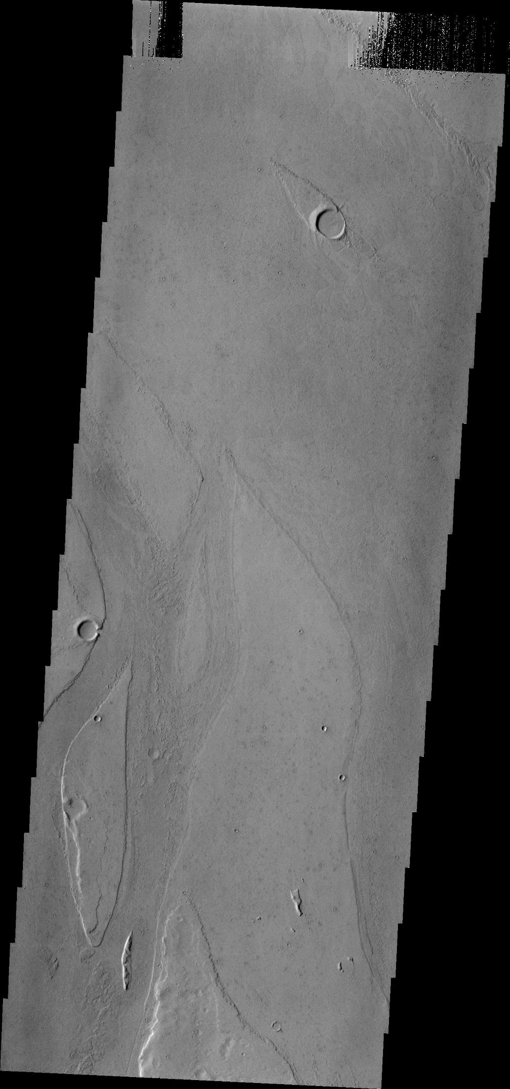 Marte Vallis, located in Amazonis Planitia, is broad and shallow. The streamlined islands at the top and bottom of the image illustrate this.