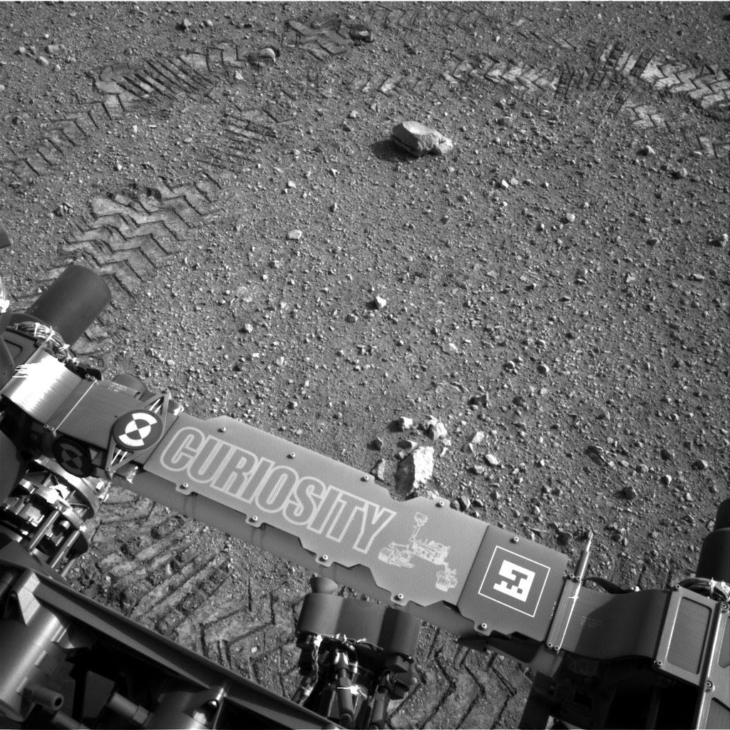 This image shows a close-up of track marks from the first test drive of NASA's Curiosity rover. The rover's arm is visible in the foreground.