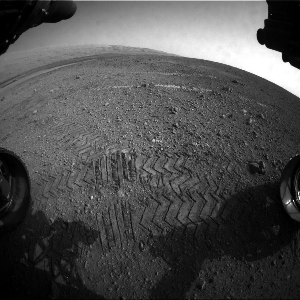 This image taken by a front Hazard-Avoidance camera on NASA's Curiosity shows track marks from the rover's first Martian drives. The rover's Bradbury Landing site and its first tire marks are seen at center, in the distance, while tracks from the second drive are in the foreground. Mount Sharp is on the horizon, which is curved to due to the camera's fisheye lens.
