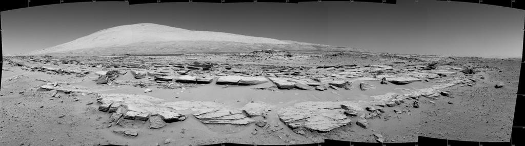 "A landscape scene from NASA's Curiosity Mars rover shows rock rows at ""Junda"" forming striations in the foreground, with Mount Sharp on the horizon. The component images were taken by the rover's Navigation Camera (Navcam), looking southward, during a pause in driving on Feb. 19."