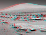 "A stereo landscape scene from NASA's Curiosity Mars rover shows rock rows at ""Junda"" forming striations in the foreground, with Mount Sharp on the horizon. The image appears three dimensional when viewed through red-blue glasses with the red lens on the left."
